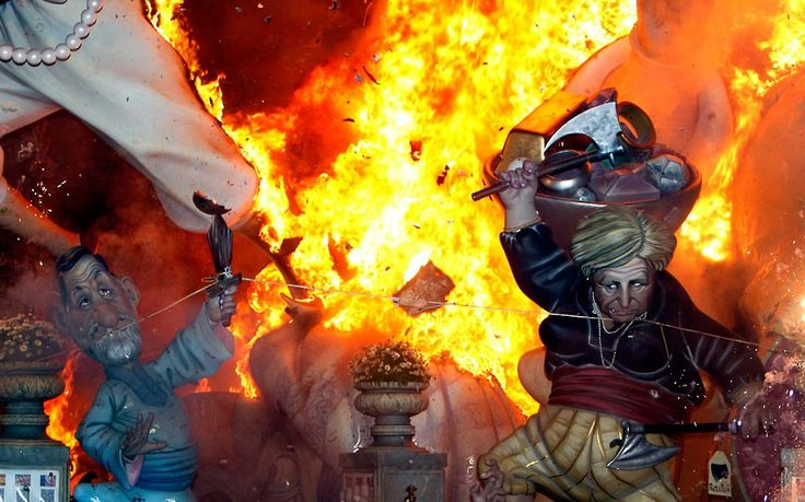 Sculptures of German Chancellor Angela Merkel and Spanish Prime Minister Mariano Rajoy are burned during the traditional Fallas Festival, in Valencia.