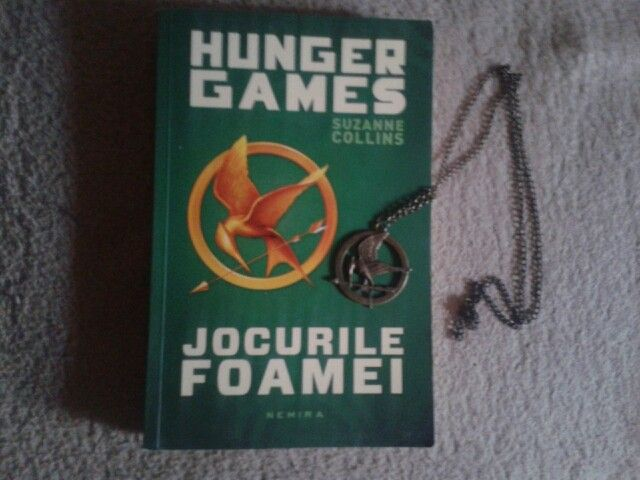 Hunger Games. The first book and the mockingjay necklace.