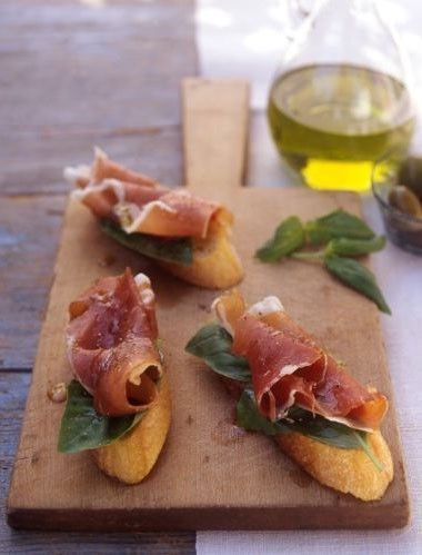 Prosciutto on bread, olive oil and basil
