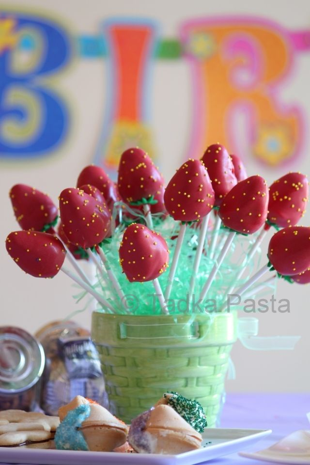 Cake Pops! The red candy shell encloses a strawberry cake center, tiny yellow sprinkles stand in for the seeds and fondant is cut to make the leaves.