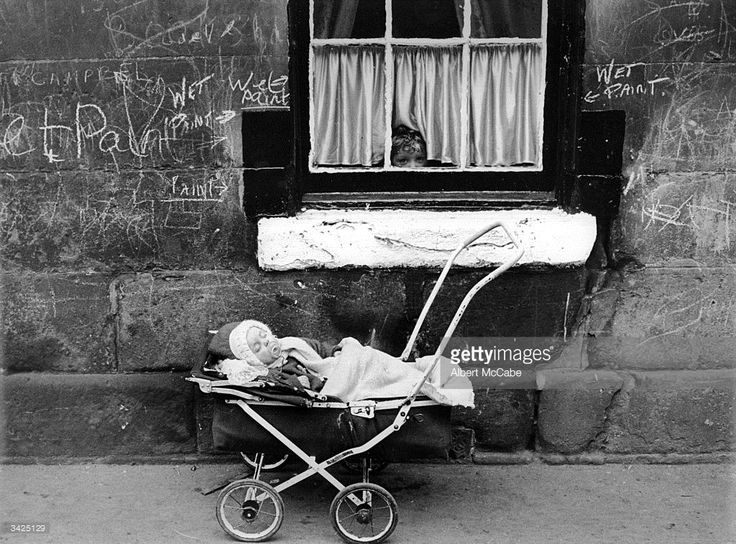 A child looks at a baby in a pram from the window of a tenement block in the Gorbals area of...