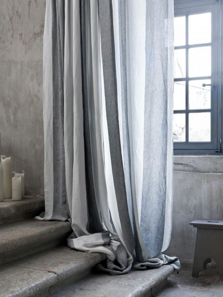 Beautifully puddled drapes, staircase, candles, wooden bench, concrete (plastered?) walls... yum
