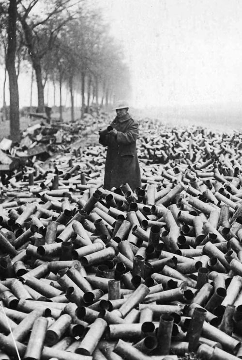 A lone British soldier stands up to his knees in spent shell cases. France, WWI.