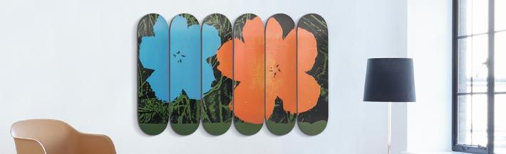 Lumas and The Skateroom present skate decks with art by Andy Warhol, Robert Rauschenberg and Jean-Michel Basquiat for supporting youth projects of Skateistan... fig.: 'Flowers' by Andy Warhol applied via screen print on six skate decks. At the image, the Andy Warhol Flowers skate decks wall art is shown in a modern living room. The Lumas X The Skateroom art skate decks are limited editions. Photo: © Andy Warhol, lumas.com_mood