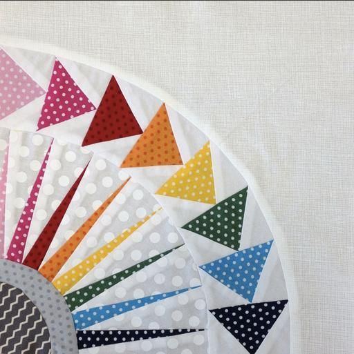 Circular Quilt with Colorful Flying Geese Along Edge