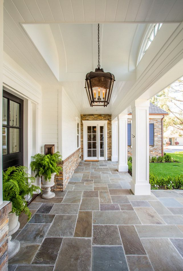 Stone Home Exterior with white siding and stone porch flooring. Stone Home Exterior. Legacy Custom Homes, Inc.