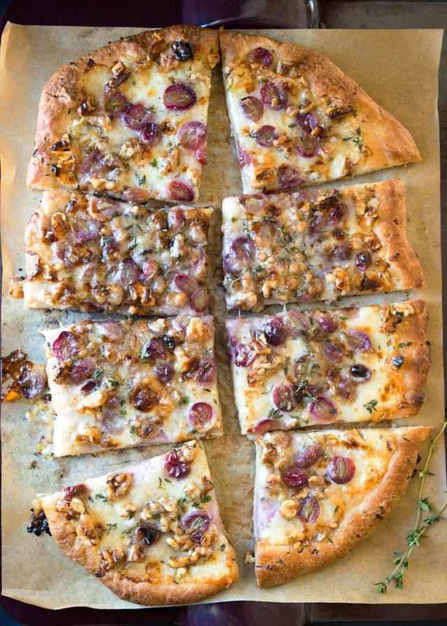 It's amazing what you can do with a pound of pizza dough. Of course you can make a traditional pizza, but why not get a little more creative? This easy flatbread, which can do double duty as an appetizer or as a full meal, has a fun combination of grapes, Taleggio cheese, and walnuts — all on whatever pizza dough you like best.