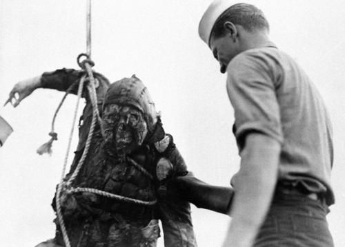 Body of a Japanese airman, KIA at Pearl Harbour, lifted from the water by the US Navy. His right hand appears undamaged; however, his face/head show signs of having suffered a high-temperature flash-fire in the brief time between his aircraft being hit and its entering the water. Why do we keep doing these things to each other ?