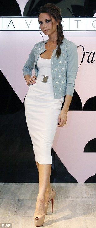 Standard posing: Victoria teamed the dress with a blue and white floral cardigan, and nude peep-toe heels