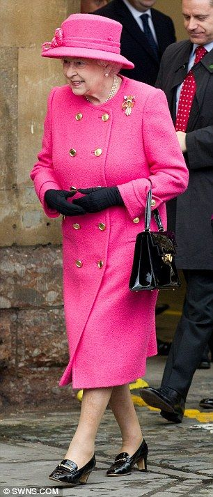 The Queen wore a spectacular cerise coat and hat - cutting a swathe through the gloomy November day as they stepped off the Rpyal train for their visit to the Bailey caravan factory in Ashton Vale, Bristol