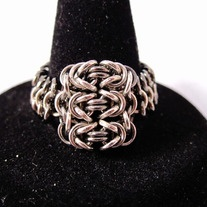 "By hand-weaving almost 200 super-tiny jump rings (1-2mm diameter), this beautiful mesh ring features 3 ""byzantine"" chainmaille units, connected to a european 4-1 band that forms the rest of the ring.      Amazingly comfortable to wear.  Available in two different designs: silver, and silver with dark accents.        SIZES   (approximate"