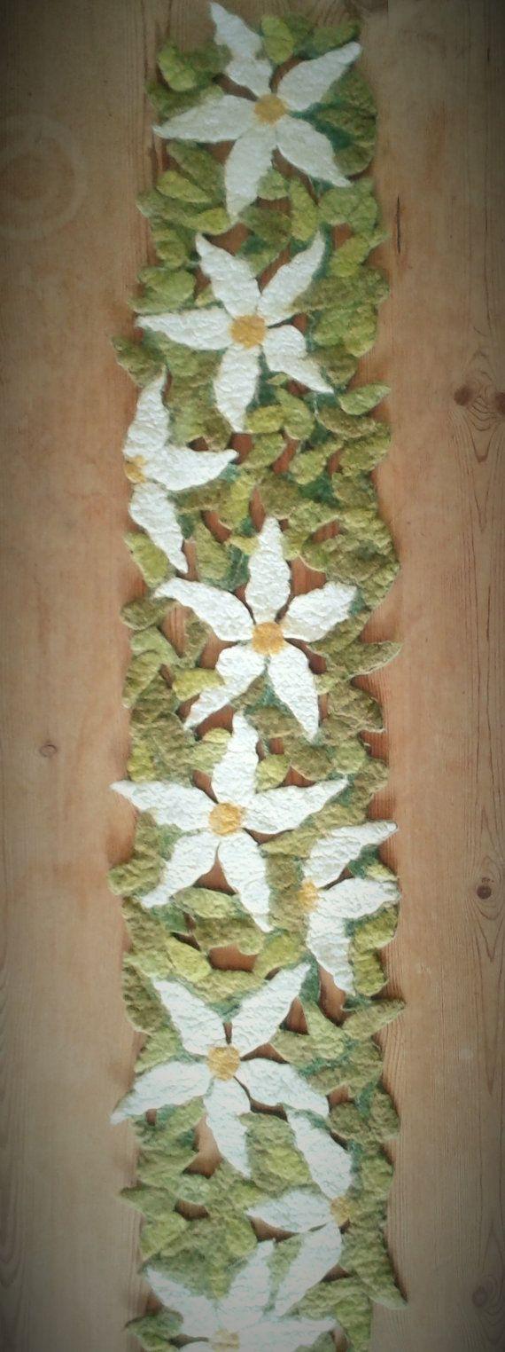 Un corridore di grazioso tavolo realizzato in lana merino, con un anello per appendere cuciti in una delle estremità. Io ho infeltrito insieme grande clematis bianco fiori su uno sfondo di foglie verdi, con spazi tra intagliate e a mostrare il colore della parete o della tabella. Una bella atmosfera estiva a qualsiasi tabella. Questa misura circa 129cms (51) L x 26cms (10) al suo  punto più largo.