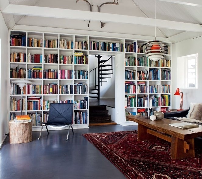 I love that the book shelves form a wall and that there are steps up to the  next room as well as a spiral staircase