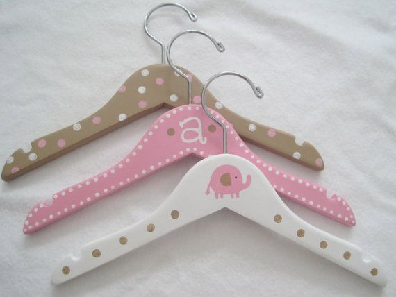 This listing is for a set of three baby hangers. Each wooden hanger is sanded, primed, painted and sealed. The hangers are painted in baby pink, white, and beige colors. Please indicate the letter you would like to have on the pink hanger in the message to seller box at checkout.