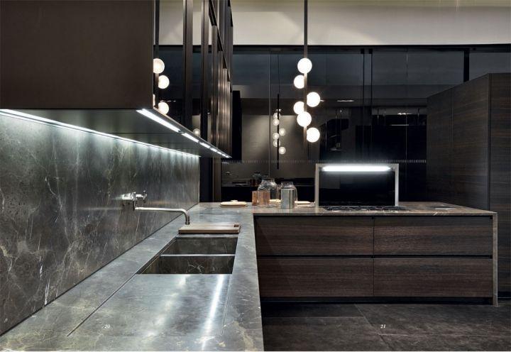 Il top, lo schienale e il lavello della cucina Trail di Varenna nella versione in pietra Stone Brown levigato. Pensili a vetrina con profilo in alluminio anodizzato