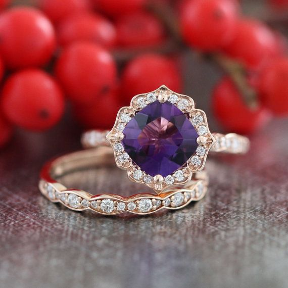 This vintage inspired bridal wedding ring set showcases a floral engagement ring with 8x8mm cushion cut natural purple amethyst set in a solid 14k
