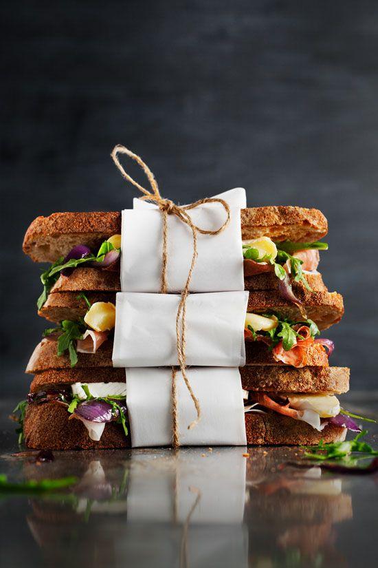 Sandwich with Brie, prosciutto, caramelized onion and arugula.