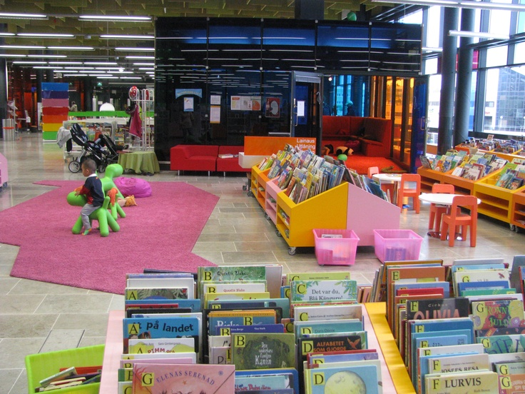 Children's area in Entresse Library, Espoo - bright colours, asymmetrical rug, coloured glass soundproof story room.