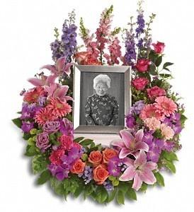 A mix of dramatic flowers such as purple orchids and asters, orange, dark pink and lavender roses, pink and peach carnations.