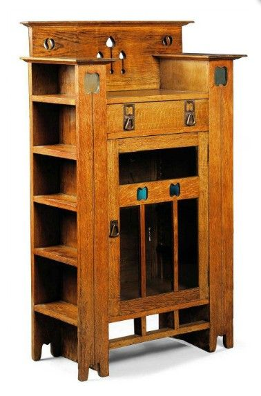 AN ARTS & CRAFTS OAK DISPLAY CABINET/BOOKCASE  CIRCA 1900  HAVING PIERCED MOTIFS AND COLOURED GLASS INSETS, WITH FRIEZE DRAWER, GLAZED DOOR ENCLOSING SHELVES, AND WITH SIDE SHELVING 54 1/8 IN. (137.2 CM.) HIGH; 33½ (85 CM.) WIDE; 16 IN. (40.7 CM.) DEEP
