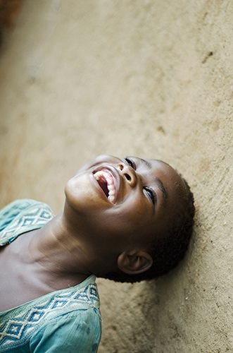 Portrait of smiling girl looking up in classroom. Malawi, Lilongwe, Kauma Community Based Childcare Centre.