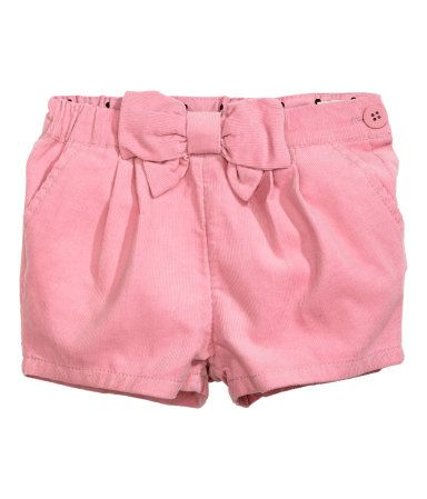 Pantalón corto de pana con pliegues en la cintura, lazo grande delante, bolsillos al bies, cinturilla ajustable y botón en un lateral.