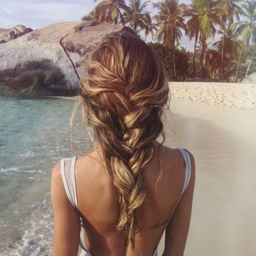 Thin sandy blonde braid tucked under loose waistlength fishtail braid, tan back, lt. grey straps; tan beach, brown rock, teal water, palms