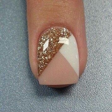 Preciosas uñas con diseños triangulares en beige, marrón y con brillos dorados.