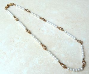 A vintage dainty faux pearl single strand necklace by Napier.  The necklace is formed from lovely creamy white faux pearls, all uniform in size, set in groupings of six, which are separated by a single pearl set in gold tone wire work