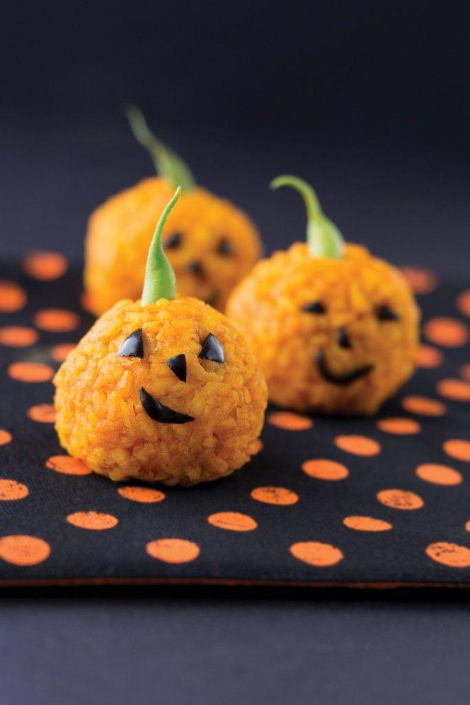 Lanternes d'Halloween réalisées avec du riz parfumé et coloré. Les yeux, la bouche et le nez peuvent être faits avec des morceaux d'olive. La queue de la citrouille est une queue de haricot vert