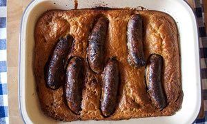 A toad in the hole has sausages in Yorkshire pudding batter.
