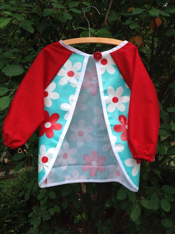 Stylish art smock for children. Front and back are waterproof laminated cotton blend, sleeves are breathable cotton. Front pockets for art