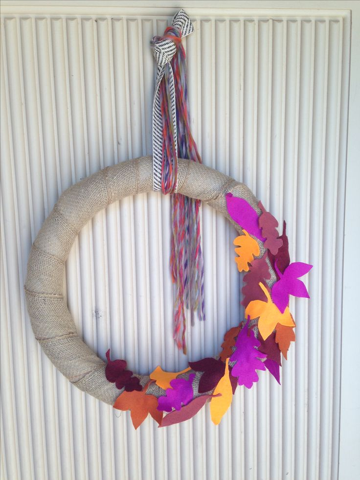 Burlap wrapped wreath with bright felt cutout leaves. Multicolored yarn hanging accent.