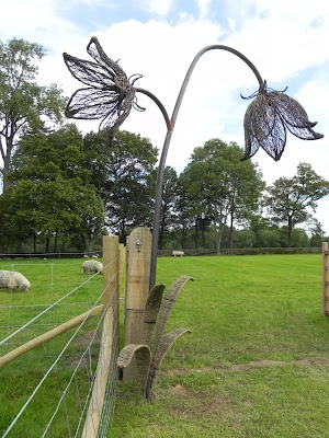 by Tom Hare ~ Willow Man | Giant Harebell sculpture, woven in brittany blue on mild steel arching over the gate which leads into the production seed beds.