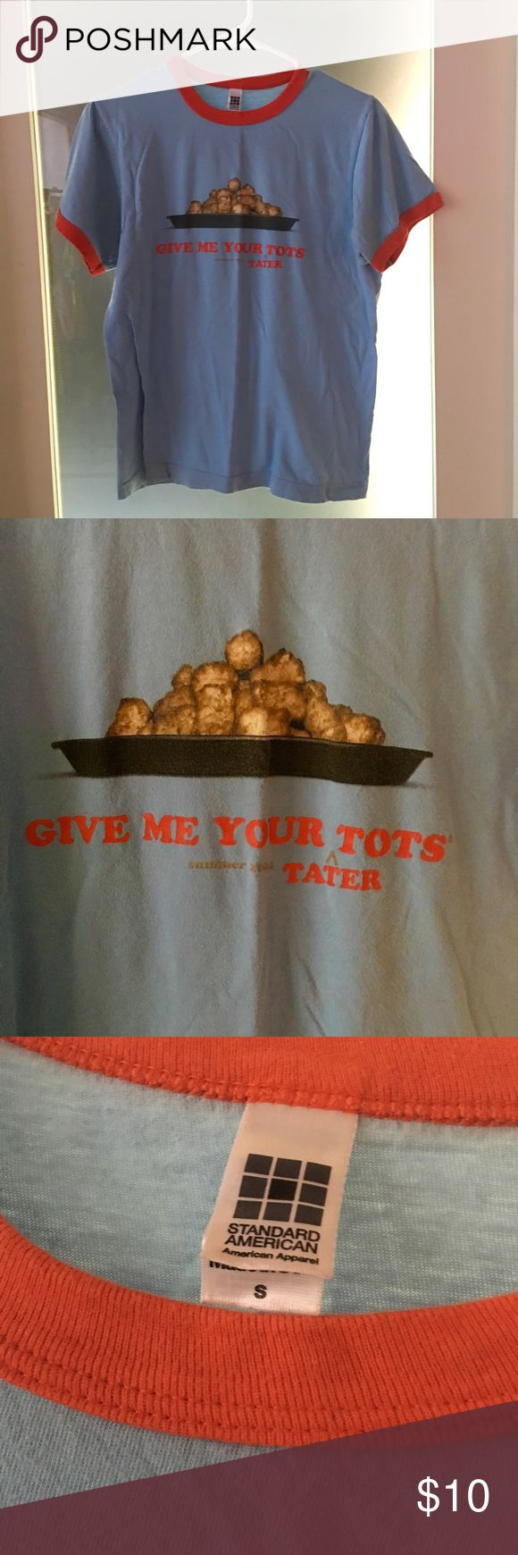 """Napoleon Dynamite Tots Crew Neck Tee Napoleon Dynamite """"Gimme your {tater} tots"""" crew neck short sleeve tee. Promotional product from the film, says """"Summer 2004"""" under the front text. Light blue shirt with orange on edges of neck and sleeves. Front has photo of tots with """"Gimme your tater tots"""" written under it (tater is being inserted before tots, since Napoleon simply called them tots).  Back says """"Napoleon Dynamite"""".  Size is a men's small, so closer to a loose women's medium or tight…"""