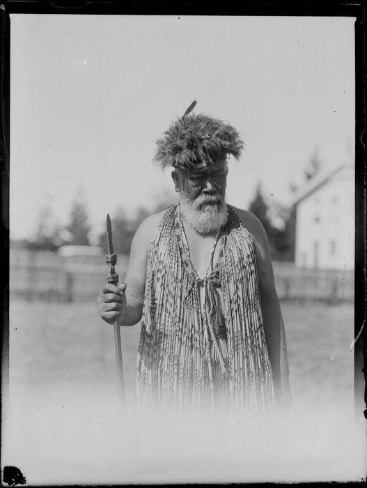 Paramount Te Arawa chief Mita Taupopoki wearing headdress and holding tiaha, [Rotorua?]   Date: [between 1925-1935]  Ref: WA-25303-G  Photograph taken by Leo White