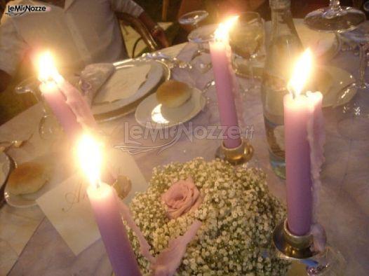 http://www.lemienozze.it/gallerie/foto-fiori-e-allestimenti-matrimonio/img15038.html Allestimento dei tavoli del ricevimento con candele viola e nebbiolina tra i fiori per il matrimonio