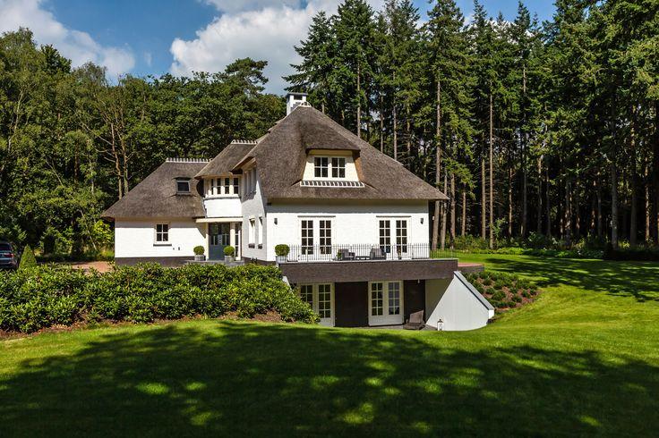 Rietgedekte, wit gekeimde villa tussen de bomen