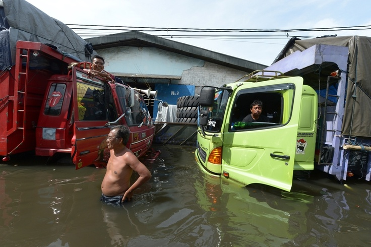 DIRE STRAITS: Indonesian drivers sat with their flooded-out trucks in the Penjaringan subdistrict of Jakarta on January 20, 2013. Police say floods in Indonesia's capital have killed at least 26 people and sent more than 100,000 fleeing their homes | © Adek Berry | AFP | Getty Images