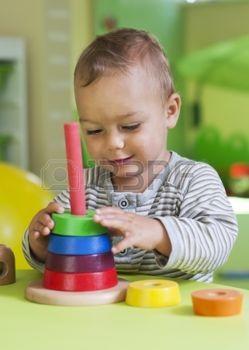 nursery+education%3A+Kleine+peuter+of+een+baby+kind+spelen+met+raadsel+cirkel+vormen+op+een+laag+tafeltje+in+een+kleurrijke+kinderen+kamer+in+een+kinderdagverblijf+of+kleuterschool.+Stockfoto