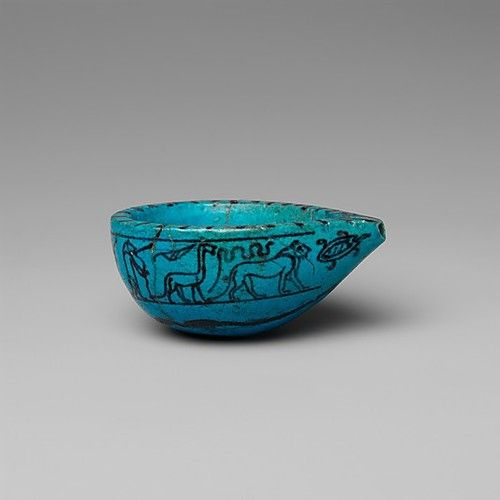 Egyptian faience feeding cup for babies and infants. The decoration on the sides is the same as those on magical wands, used for the protection of the child. From left to right: the goddess Taweret, a griffin, a snake, a lion and a turtle. Found in Lisht, the Memphis area, in the west corner of the pyramid cemetery. Middle Kingdom, 12th dynasty, 1850 - 1700 BCE. Metropolitan Museum