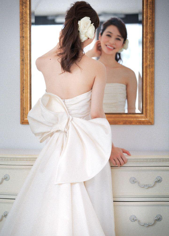 アシンメトリーなバックに釘付け♪飾りのないシンプルなドレスには、あえて背中のリボン1点で魅せるのがオトナ流。