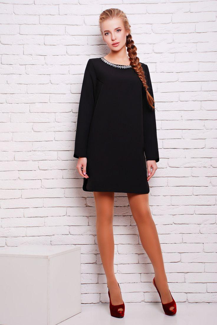 Платье с декором ожерелье цвет черный  НОРМА - Коктейльное универсальное однотонное платье из плотного дорогого трикотажа длиной мини. Платье выполнено в минималистическом лаконичном стиле. А-образный силуэт платья очень демократичен и позволяет скрыть незначительные недостатки фигуры. Рукав свободный, длинный. По боковому шву подола красивые закругленные вырезы, которые повторяются по низу рукава. Изюминкой наряда стал декоративный элемент на круглой горловине в виде ожерелья из стразов.