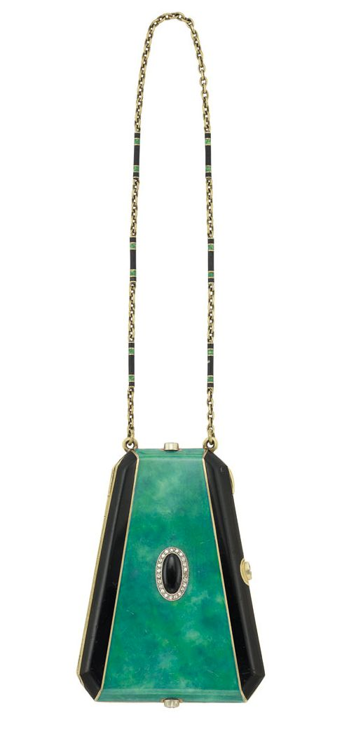 Circa 1920 Art Deco Gold, Enamel, and Diamond Vanity with Carrying Chain. The trapezoidal-shaped vanity applied with black and variegated bluish-green enamel, centering an oval black enamel plaque surrounded by single-cut diamonds, completed by a gold carrying chain composed of oval links spaced by elongated baton links applied with black and green enamel, with mirror, powder and make-up compartment. Sold for $4,000 at Doyle New York auction.