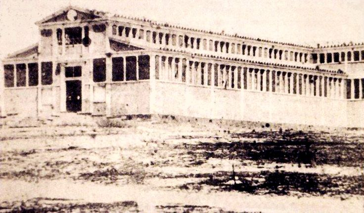https://flic.kr/p/r7SHN3   Building of the Olympians 1859   This was a wooden construction built in 1858 as an exhibition centre, located on the land arrogated for the building of Zappeion, and specifically near the junction of Amalias with Olgas. It housed exhibitions in 1859, 1870 and 1875. With the completion of the permanent exhibition centre known as Zappeion, it was demolished in 1887. Image file source: okeanis.lib.teipir.gr/xmlui/handle/123456789/334 Public Domain image