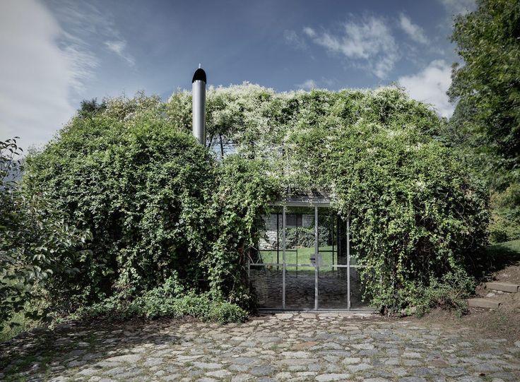 Le studio italien Act_Romegialli a été chargé de réaménager le garage d'une maison de vacances en un espace pour se détendre et se divertir. Le studio a collaboré avec l'architecte paysagiste Gheo Clavarino afin de créer cette boîte verte. Ils ont conservé le mur de pierre et les colonnes initiales du garage puis ont ajouté un cadre métallique pour supporter les panneaux vitrés et le toit en pente. Une végétation abondante et grimpante recouvre magnifiquement la structure, lui permettant...