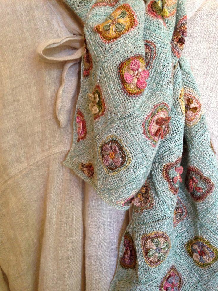 Un plaid au crochet avec fleurs en relief et couleurs tendres.
