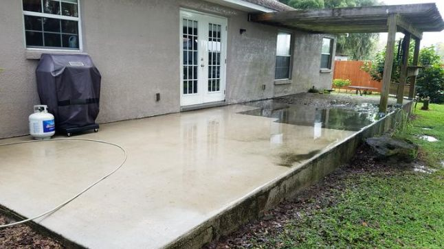 Halfway done pressure washing  a back concrete patio. Check it: