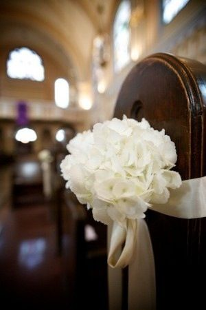 Hydrangea pew end tied with purple ribbon