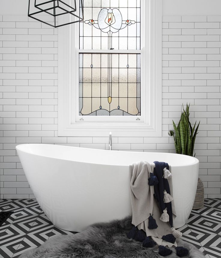White brick walls, stain glass window, stand alone tub and black and white patterned tiled floor | GIA Renovations